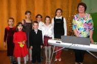 Skolotāja Inga Lūse ar vokālā ansambļa dalībniekiem.